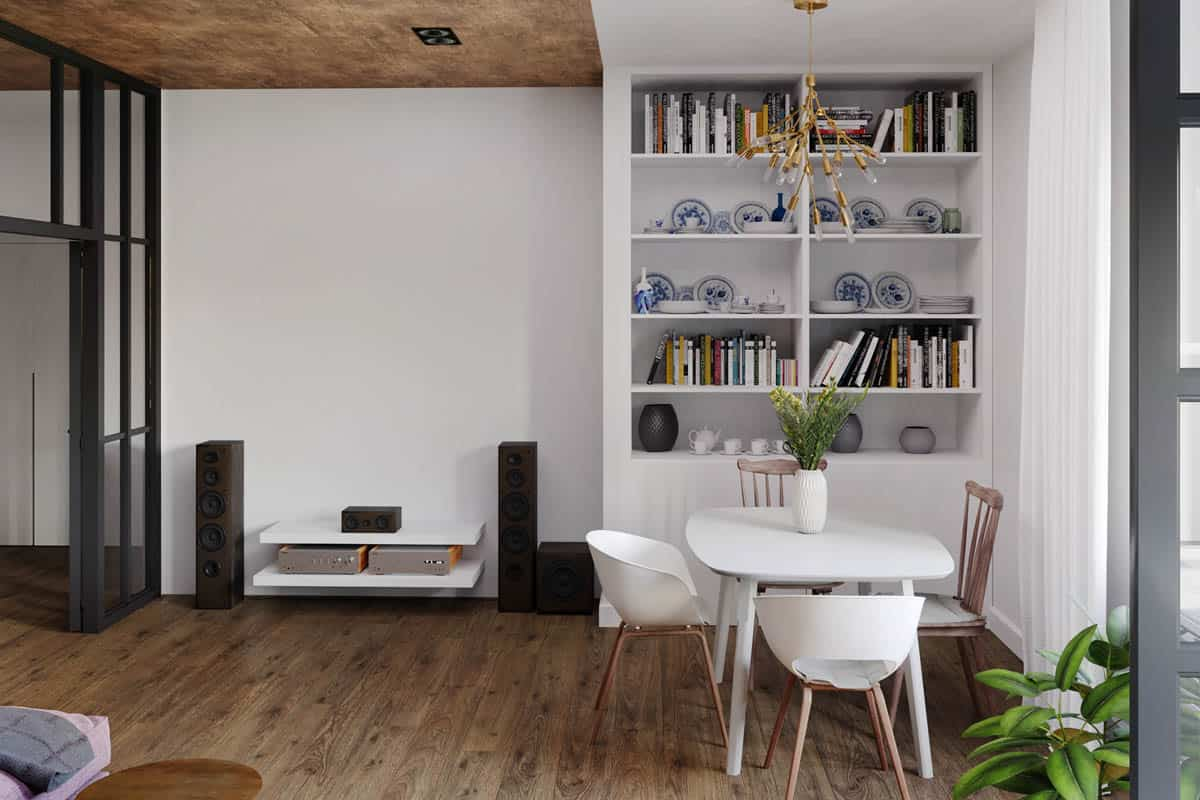 This is a look at the opposite wall of the sofa with an entertainment setup next to a built-in white wooden structure with shelves.
