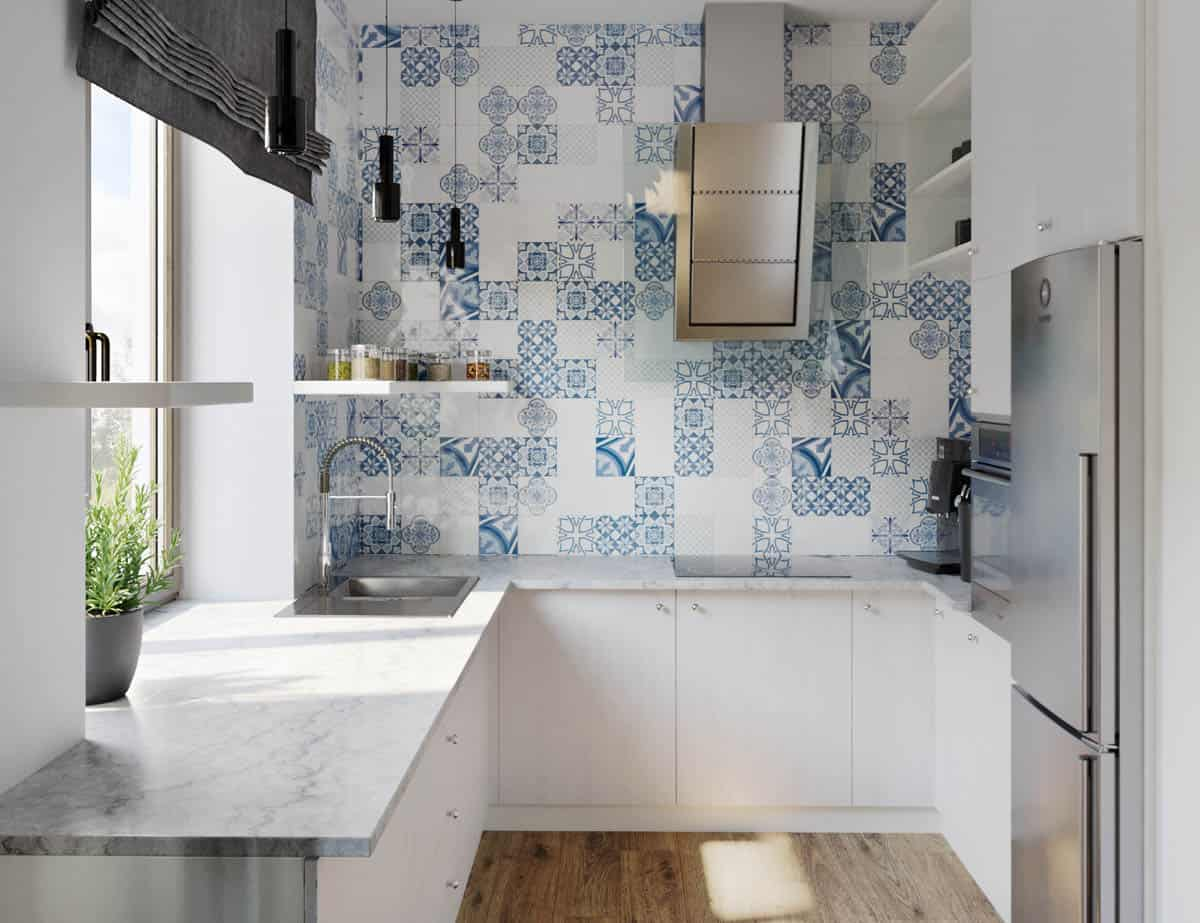 The kitchen also has a large patterned blue wall on the side of the cooking area and sink area making the stainless steel vent stand out.