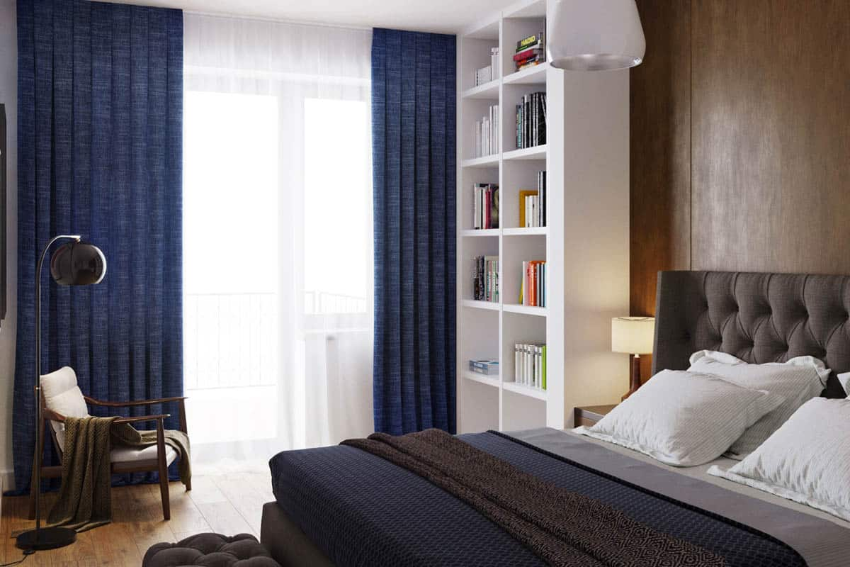 The side of the white wooden bookshelf of the bedroom is a large curtained window that brings in natural lighting and has a reading nook on the side.