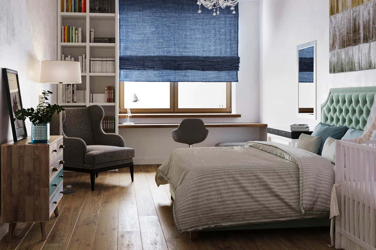 On the side of the bed is a large window with a built-in desk underneath and a bookshelf on the corner.