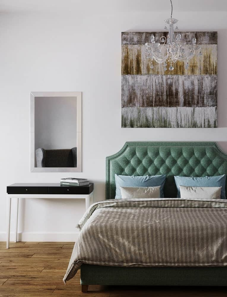 This other bedroom has a bed with green tufted headboard to stand out against the white wall topped iwth a painting.