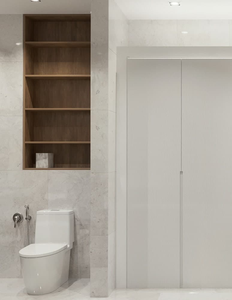 The white toilet is topped with a built-in wooden shelving that is embedded into the wall that has the same white marble tiles as the floor.