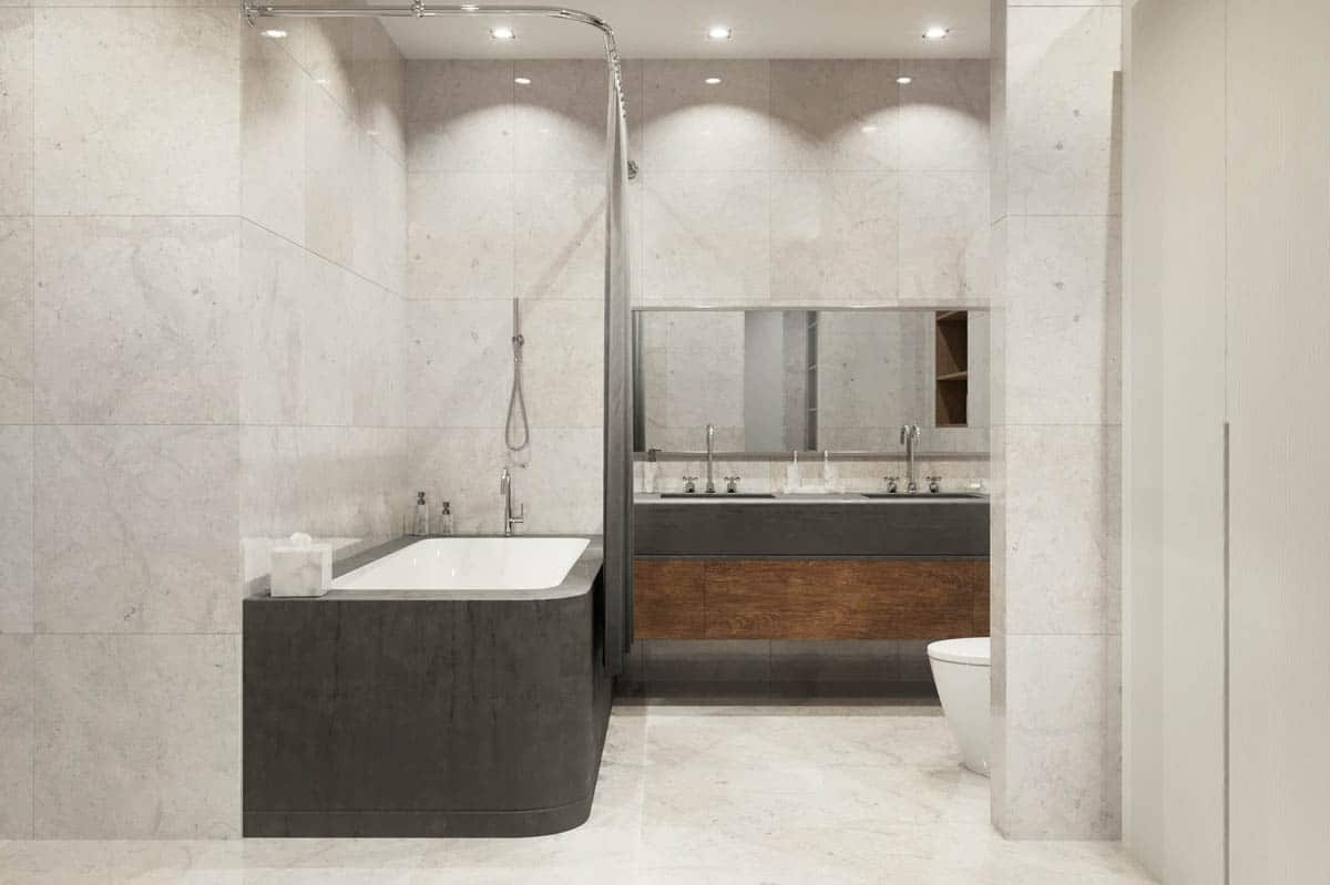The bathroom has a large bathtub on the left side beside the two-sink vanity with gray and wooden tones.