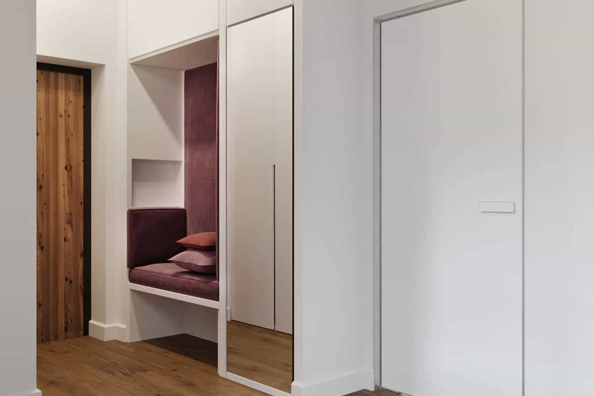 At the side of the wooden main door of the apartment is this built-in cushioned bench with purple tones on its cushions and pillows to stand out against the white walls with a mirrored panel.