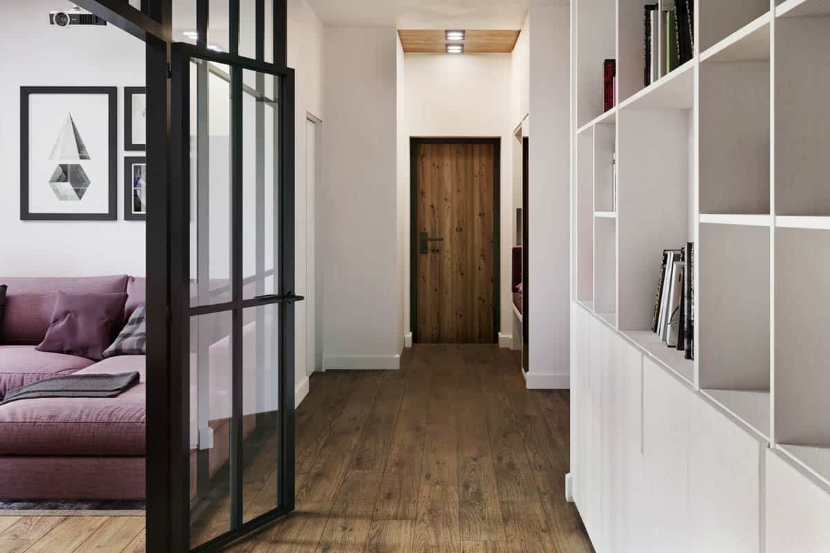 The long hallway foyer of the paartment has a wooden main door that has the same wooden tone as the hardwood flooring and the ceiling.