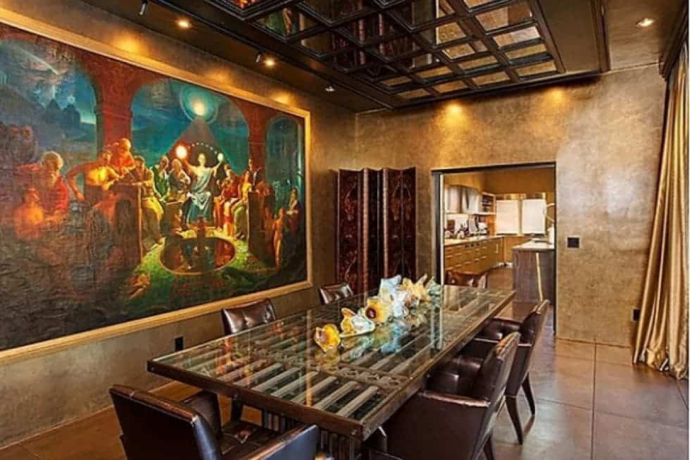 The dining room has a large colorful painting mounted on one wall looking over the long dining table surrounded by brown leather chairs. Image courtesy of Toptenrealestatedeals.com.