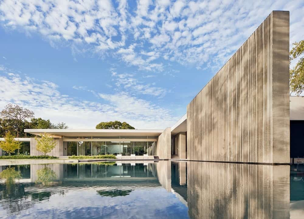 This is a view of the house from the vantage of the large pool with a tall earthy wall on the side that extends to the house with an abundance of glass walls.