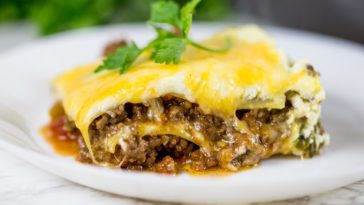 A slice of taco lasagna with melted cheese on top and layers of meat.