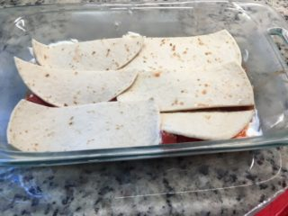 A layer of tortillas are placed on the pan.