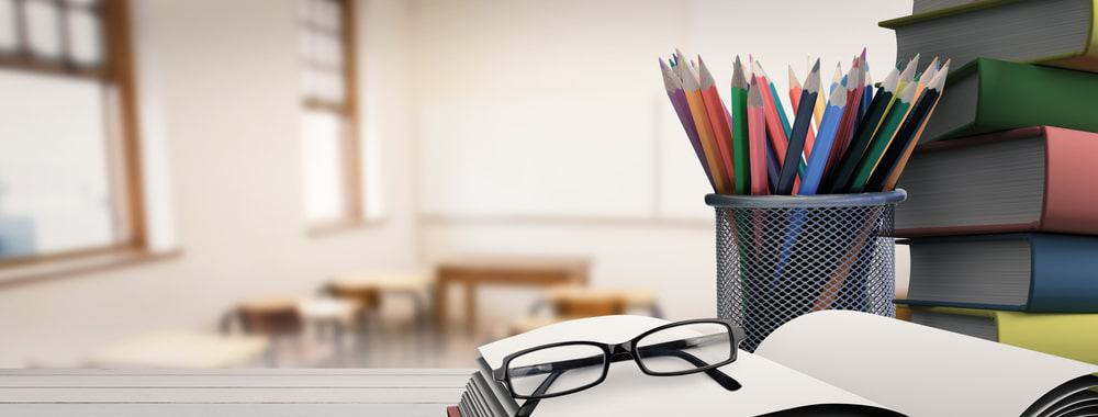 Stacked books, a can of multicolored pencils, and eyeglasses above an open book inside an empty classroom.