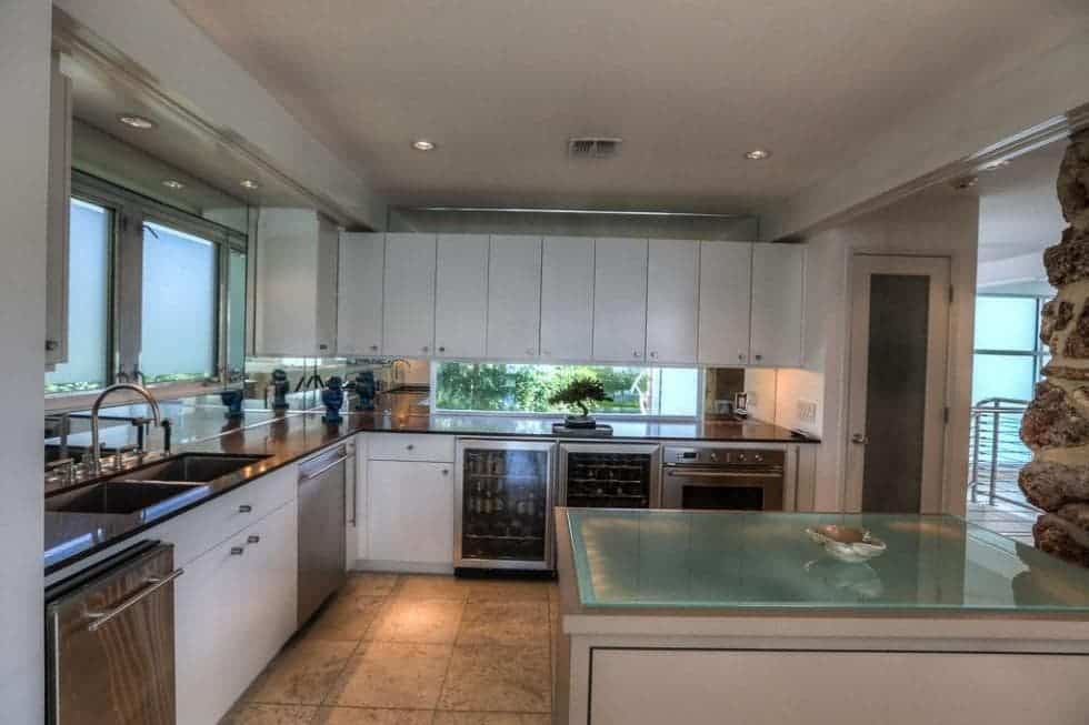 This is the kitchen with a peninsula on the side that has white cabinetry to match those lining the walls. These are complemented by the glass walls and appliances. Image courtesy of Toptenrealestatedeals.com.