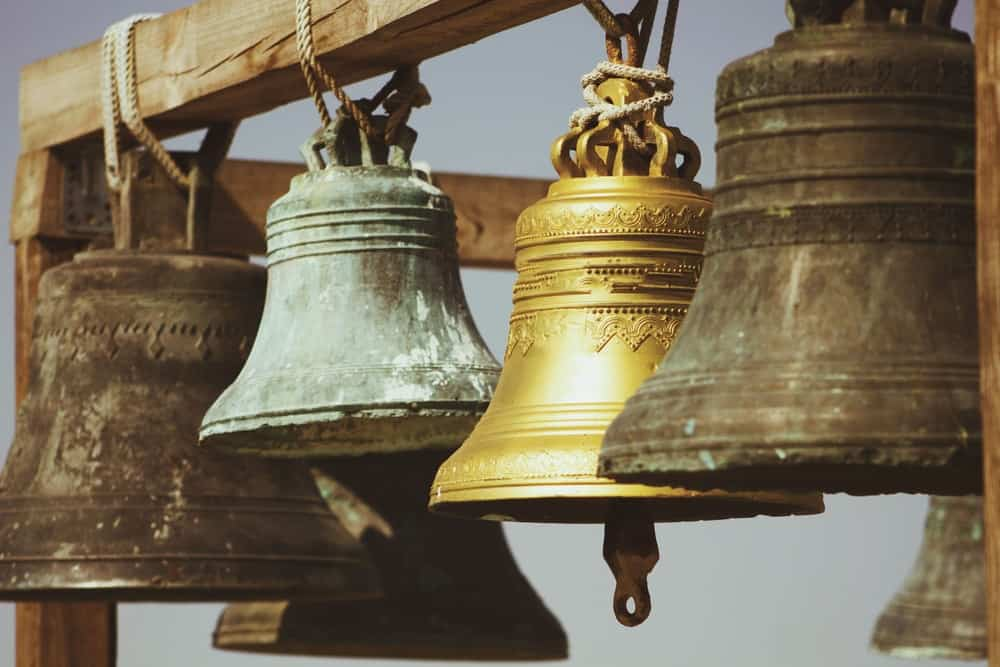 Church bells of various metals hanging on a wooden beam.