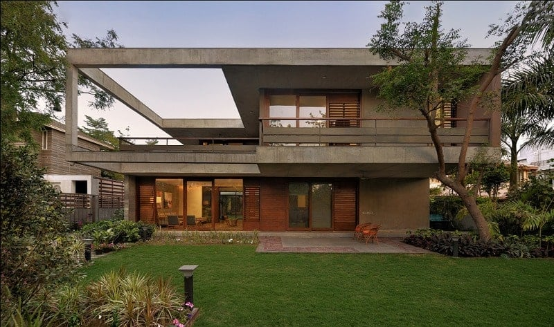 This is a view of the back of the house showcasing the concrete structures of the house complemented by the wooden elements. complemented by the landscaping of the backyard.