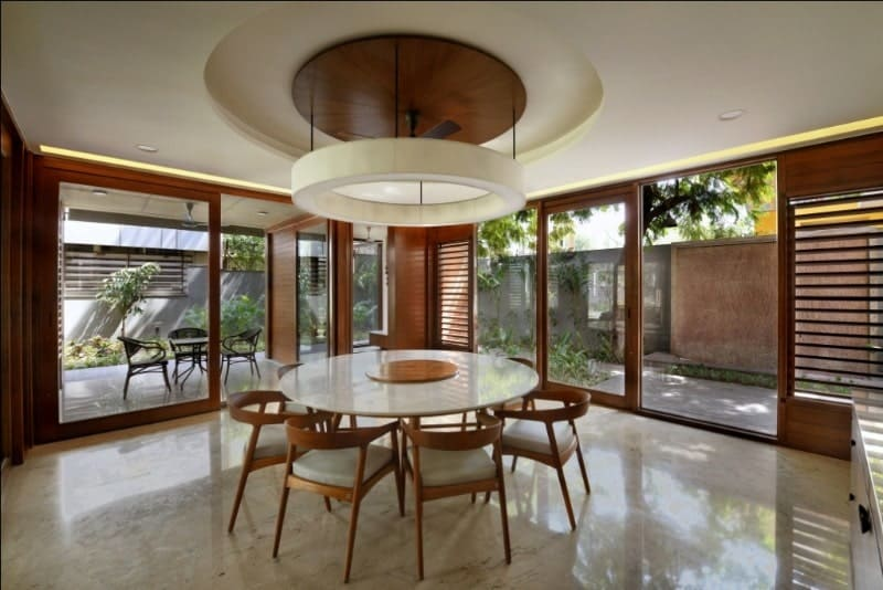 This is the dining room with a large round white dining table surrounded by wooden chairs with cushioned seats.