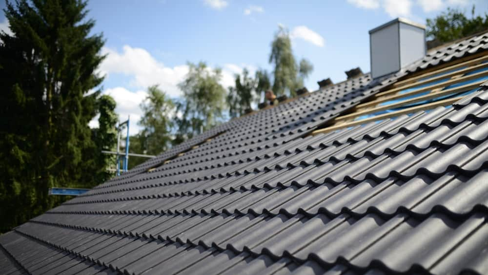A close look at the black tiles of a roof being installed.