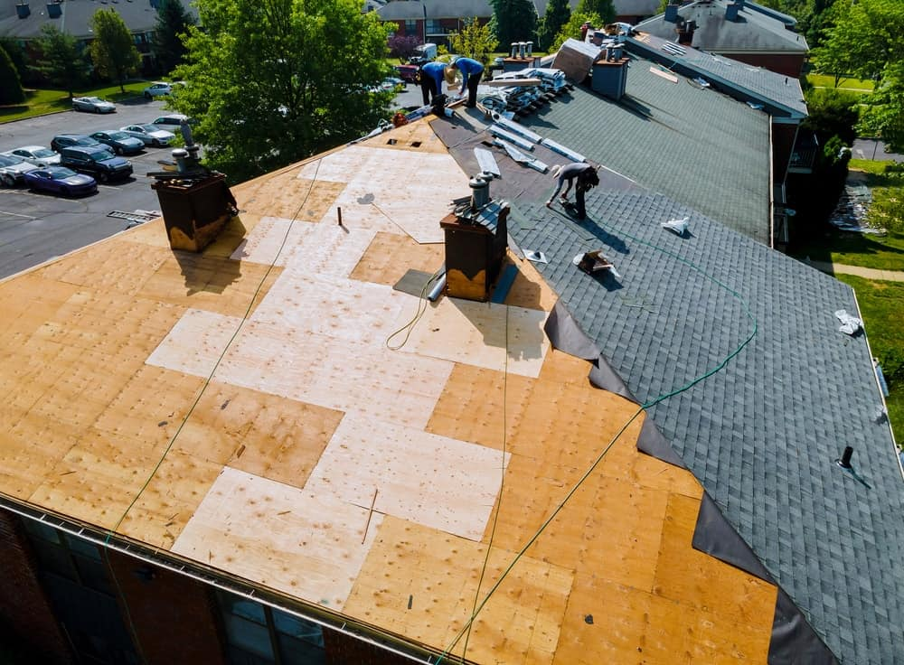 An aerial view of a group of workers repairing the roof of a house.