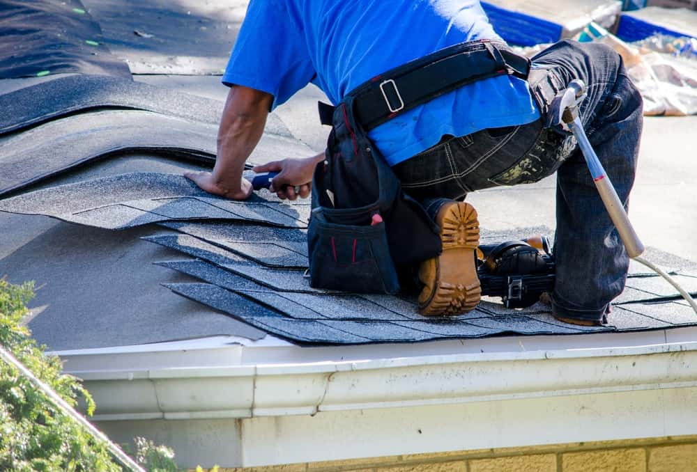 A close look at a man installing shingles on the roof.