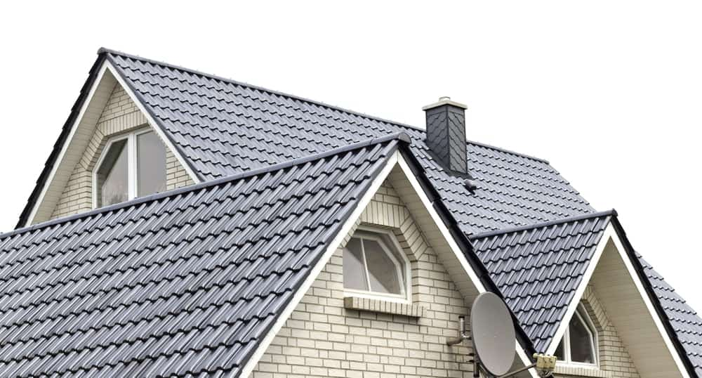 A close look at a brick house's gray roof with a chimney.