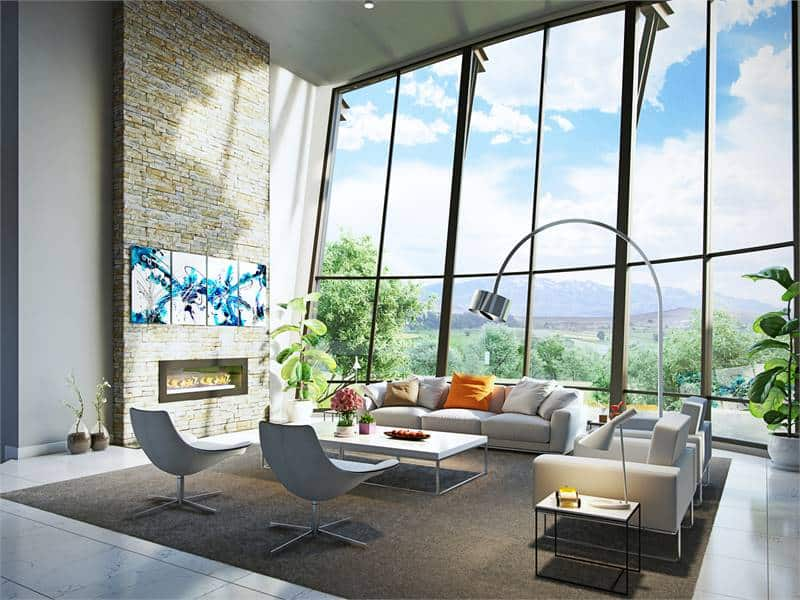 The living room has light gray seats, a modern fireplace, sleek tables, an arched floor lamp, and a floor-to-ceiling window overlooking a breathtaking mountain view.