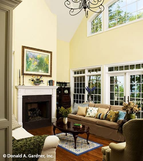 The living room has cozy fabric seats, a fireplace, clerestory windows, and a dark wood coffee table sitting on a bordered rug.