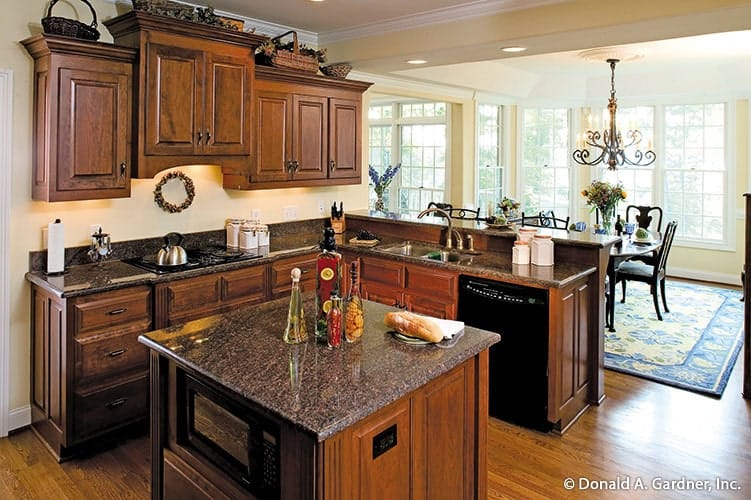 Eat-in kitchen with granite countertops, wooden cabinetry, black appliances, and a small center island.