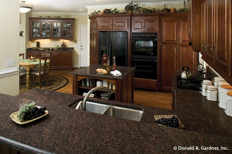 The two-tier peninsula is fitted with a double bowl sink and a gooseneck faucet.