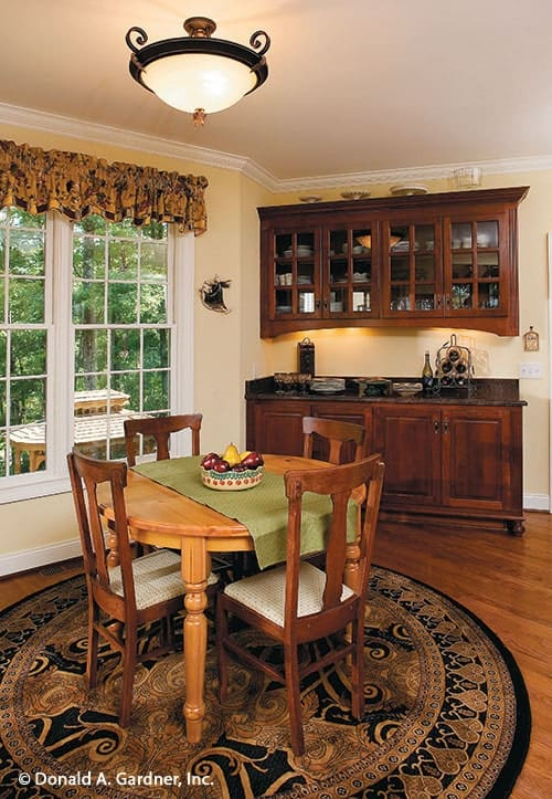 Breakfast room with buffet cabinet, round dining table, a classic area rug, and a glass dome pendant.