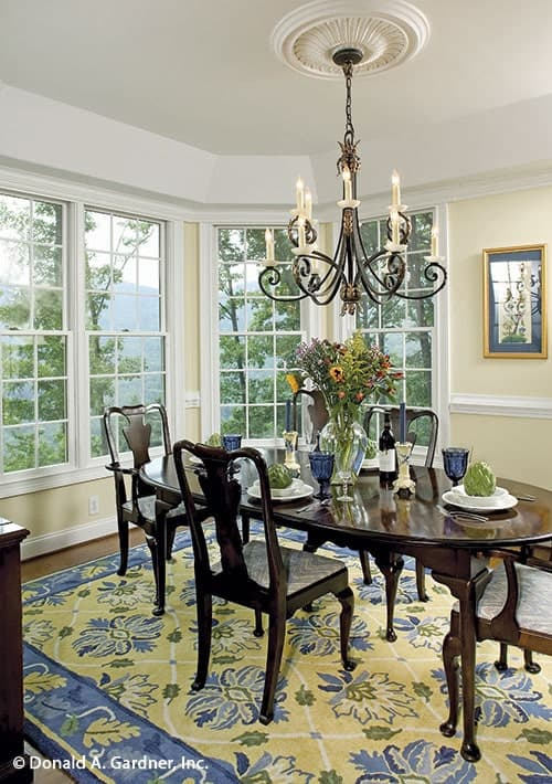 The dining area has a large floral rug, cushioned chairs, an oval dining table, an ornate chandelier, and a bay window.The dining area has a large floral rug, cushioned chairs, an oval dining table, an ornate chandelier, and a bay window.