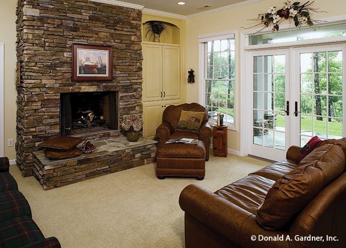 Recreation room with a stone fireplace, leather seats, white built-ins, and a french door that leads out to the rear patio.