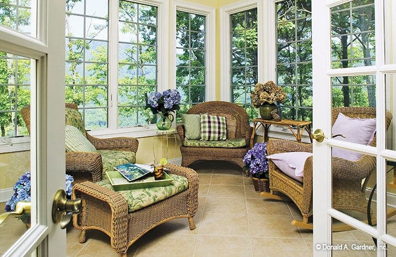 The sunroom is filled with wicker seats, wooden tables, and decorative flower pots.