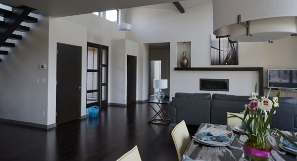 The shared dining and living room has a vaulted ceiling and dark hardwood flooring.
