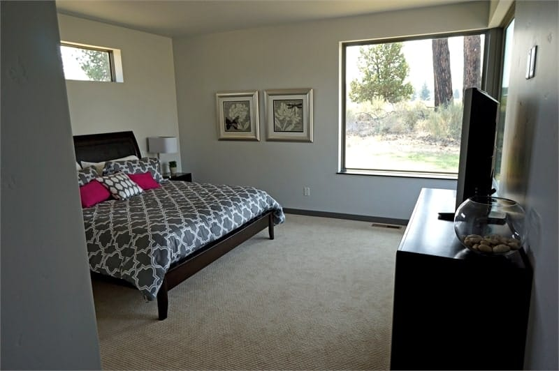 This bedroom has dark wood furnishings, carpet flooring, and picture windows overlooking the outdoor scenery.