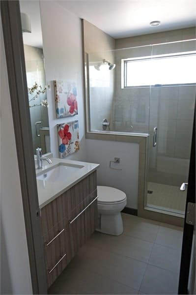 The bathroom has floating vanity, a toilet, and a walk-in shower enclosed in frameless glass panels.
