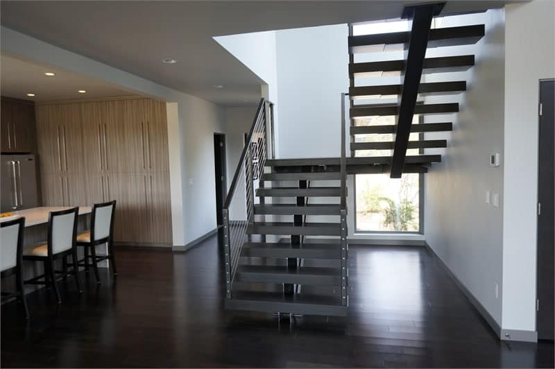 Half turn staircase with a single stringer, metal railings, and dark wood treads.