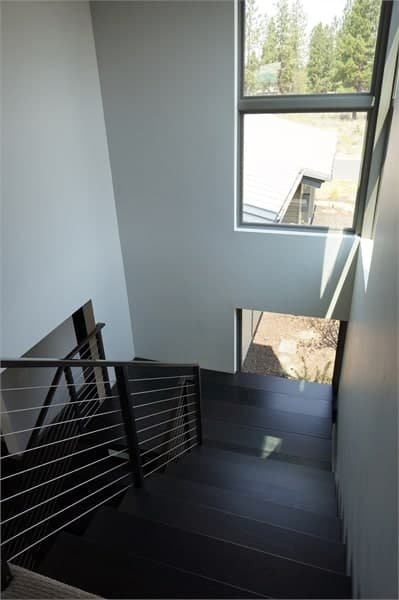 The staircase landing has wide plank flooring and glass windows that overlook the courtyard.