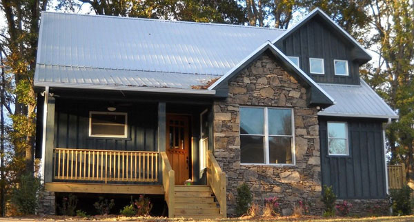 Front exterior view with stone accents and a covered porch complemented with a wooden stoop.