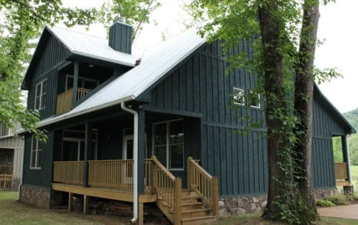 Rear exterior view with gable roofs, board and batten siding, and a covered porch.