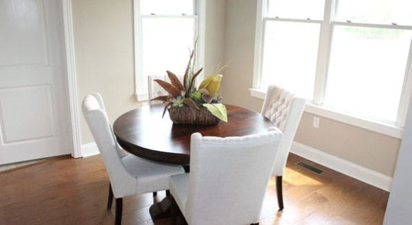 The dining area has tufted wingback chairs and a round wooden table topped with a potted plant.