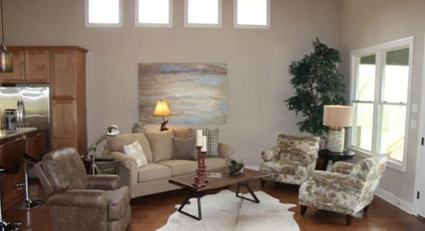 Living room with cozy seats and a wood top coffee table that sits on a cowhide area rug.