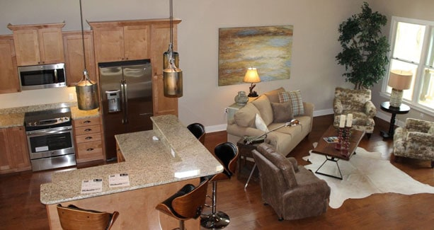 Open layout view of the living room and kitchen with natural hardwood flooring.