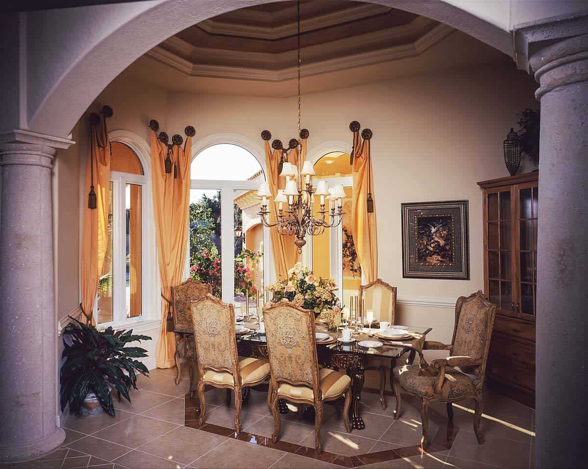 The formal dining room has classy chairs, a carved wood dining table, arched windows, and an ornate chandelier that hangs from the step ceiling.