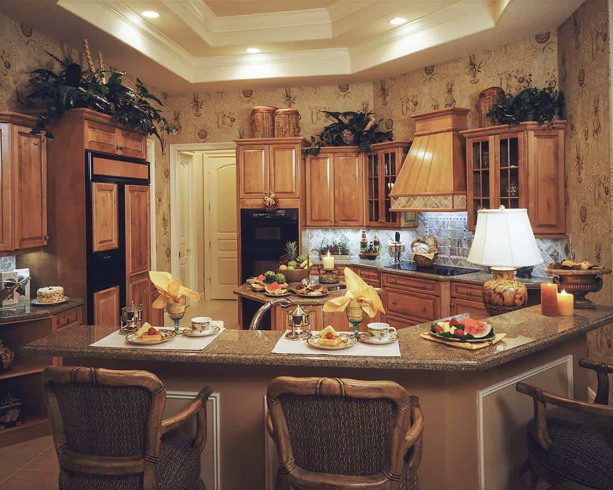 The kitchen is equipped with wooden cabinetry, black appliances, granite countertops, a small center island, and a curved peninsula.