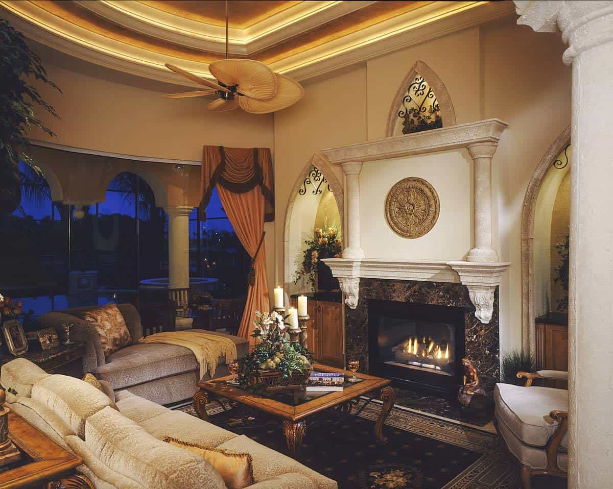Gathering room with cushioned seats, a glass top coffee table, and a marble fireplace flanked by arched built-ins.