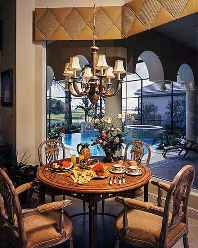 Dinette with a round dining set, a classic chandelier, and massive windows overlooking the backyard pool.