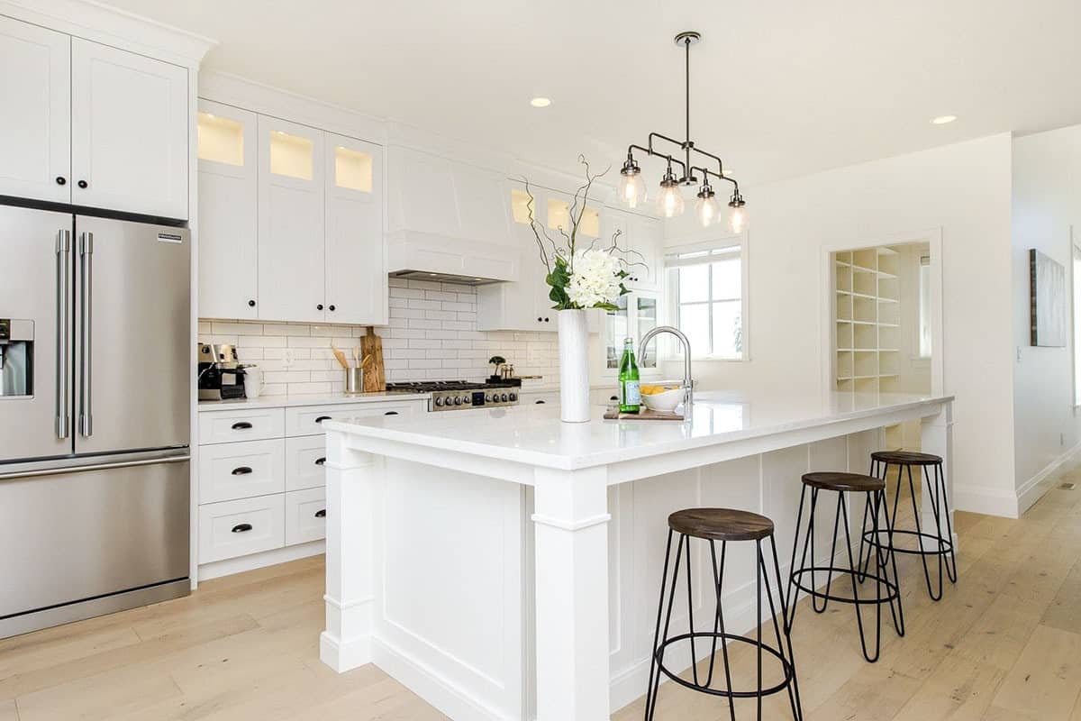 Kitchen with white cabinetry, subway tile backsplash, slate appliances, and a breakfast island.