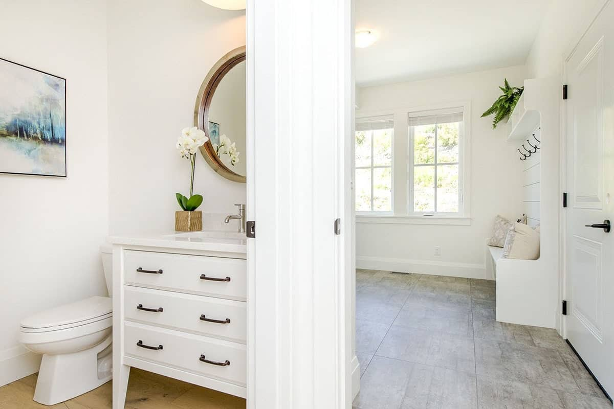 Powder room with a toilet and white vanity paired with a round mirror. The mudroom on the side offers white built-ins and framed windows.