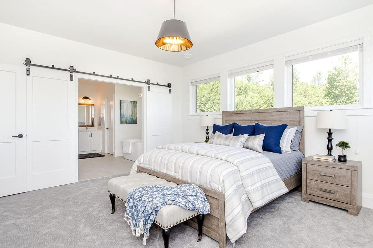 The primary bedroom has rustic furnishings, a dome chandelier, and a white barn door that opens to the bathroom.
