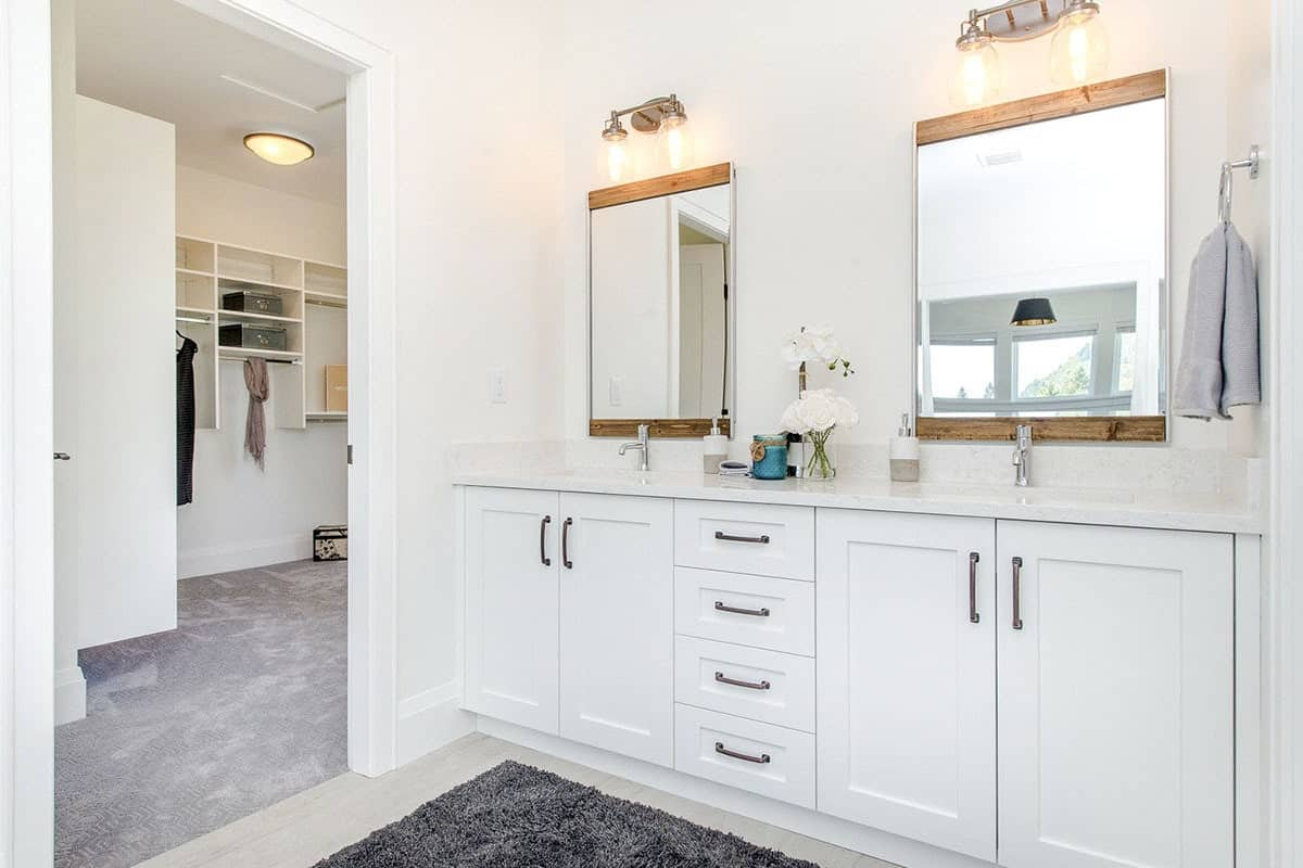 The white vanity with dual sink and matching mirrors leads to a spacious walk-in closet.