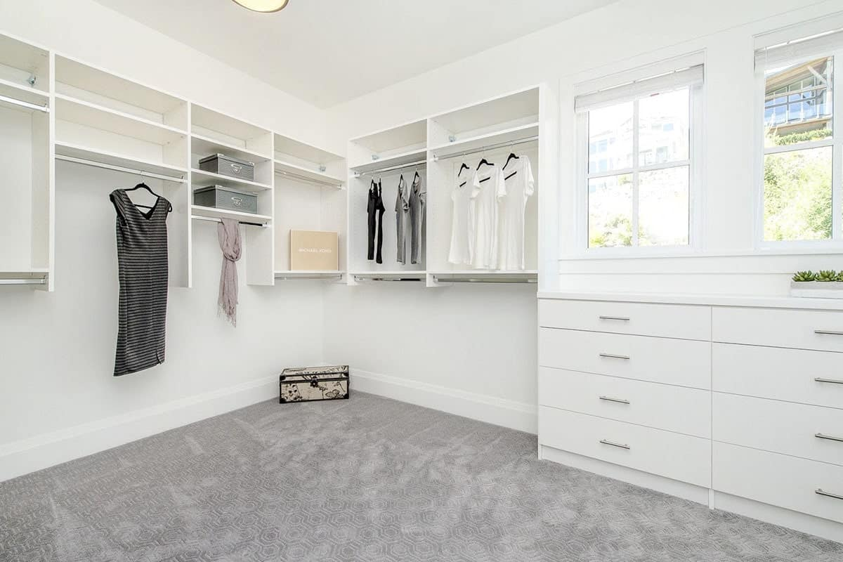 Walk-in closet with white built-ins, drawers, gray carpet flooring, and picture windows that invite natural light in.