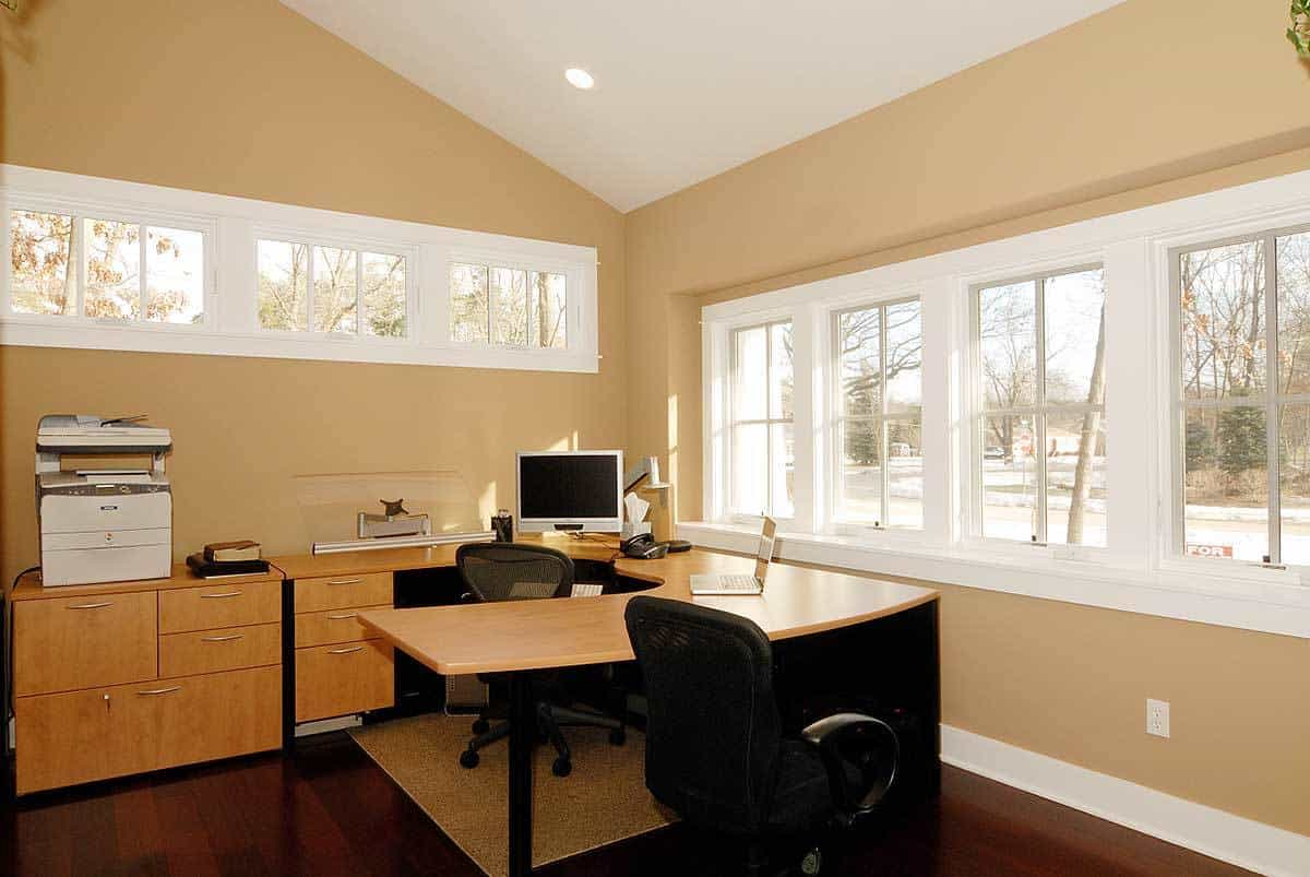 The study has a built-in desk, black swivel chairs, beige walls, and plenty of glazed windows that invite natural light in.